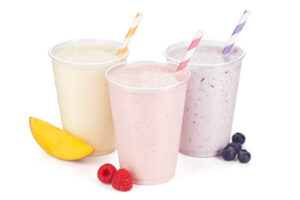 Three Flavors Of Fruit And Yogurt Smoothies Or Shakes On White