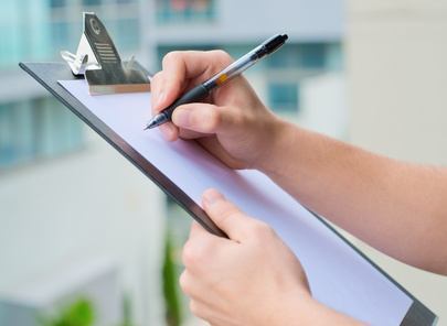 Businessman Holding A Clipboard And Writing