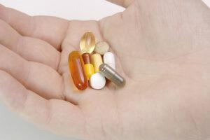 Hand Full Of Pills And Vitamins