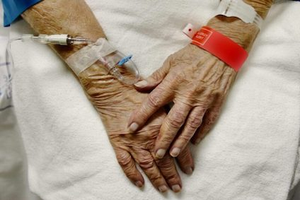 View Of Elderly Womans Hands With Ivs And Hospital Bracelets